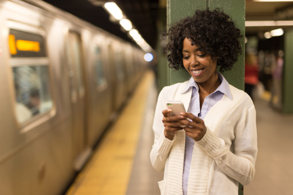 Young African American black woman in city at night texting cell phone subway station